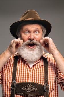 Wąsy. szczęśliwy starszy mężczyzna ubrany w tradycyjny austriacki lub bawarski strój, wskazując na szarym tle studio. miejsce. obchody, oktoberfest, festiwal, koncepcja tradycji.