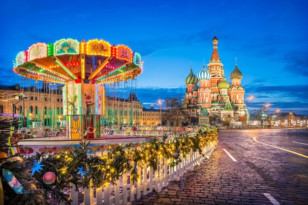 Wasyla błogosławionego pod błękitnym niebem na placu czerwonym w moskwie i karuzela dla dzieci w świetle lampionów w zimowy poranek