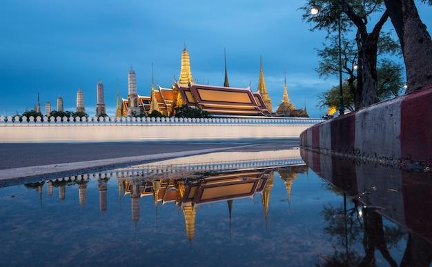 Wat phra kaew, uroczysty pałac przy zmierzchem w bangkok, tajlandia z odbiciem.