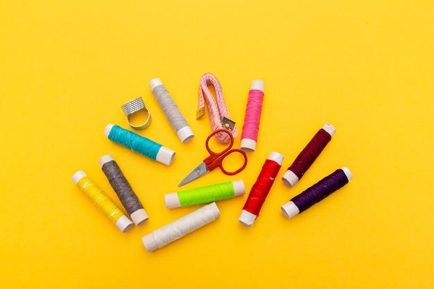 Wątek, igły, nożyczki i licznik na żółtym tle. zestaw krawiecki. zestaw do szycia w wielu kolorach