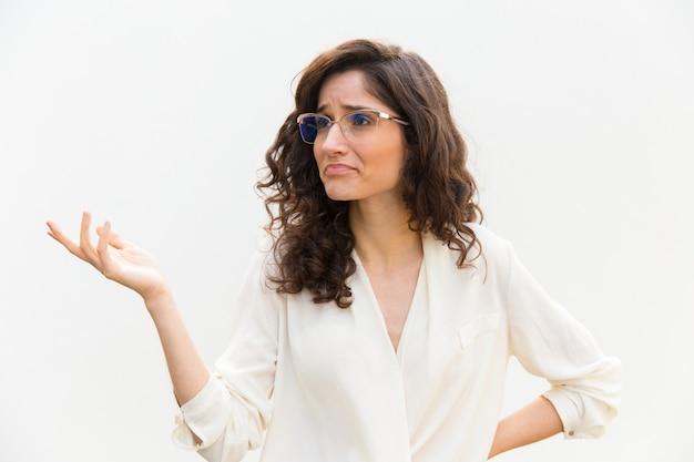 Wątpiąca młoda kobieta z wyciągniętą ręką