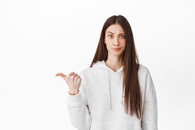 Wątpliwa i sceptyczna nastolatka marszcząca brwi, patrząca oceniającą miną i wskazująca na lewy baner z logo, pokazująca coś złego lub przeciętnego, kiepski promo, biała ściana