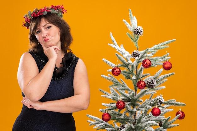 Wątpliwa kobieta w średnim wieku ubrana w świąteczny wieniec na głowę i świecącą girlandę na szyi, stojąca w pobliżu udekorowanej choinki