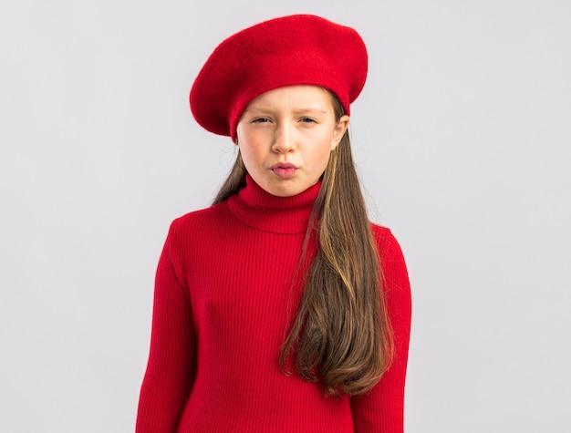 Wątpliwa mała blondynka ubrana w czerwony beret, patrząc z przodu na białym tle na białej ścianie z miejscem na kopię