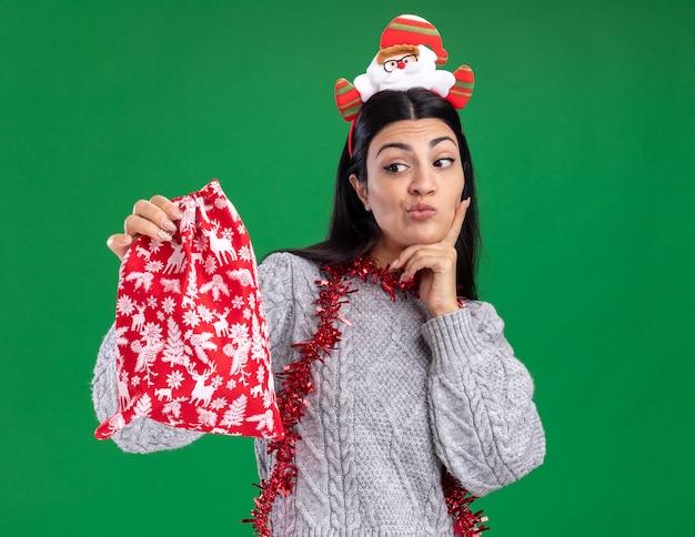 Wątpliwa młoda kaukaska dziewczyna ubrana w opaskę świętego mikołaja i świecącą girlandę wokół szyi, trzymając i patrząc na worek prezentów świątecznych, trzymając rękę na brodzie na białym tle na zielonym tle