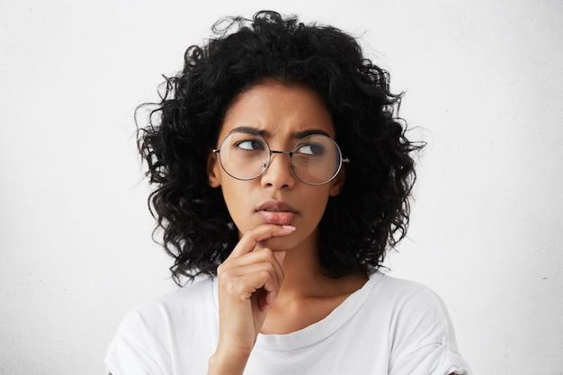 Wątpliwa młoda kobieta marszczy brwi w modnych okrągłych okularach