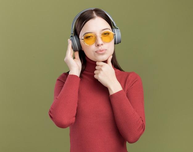 Wątpliwa młoda ładna dziewczyna w okularach przeciwsłonecznych i słuchawkach dotykająca słuchawek trzymając rękę na brodzie
