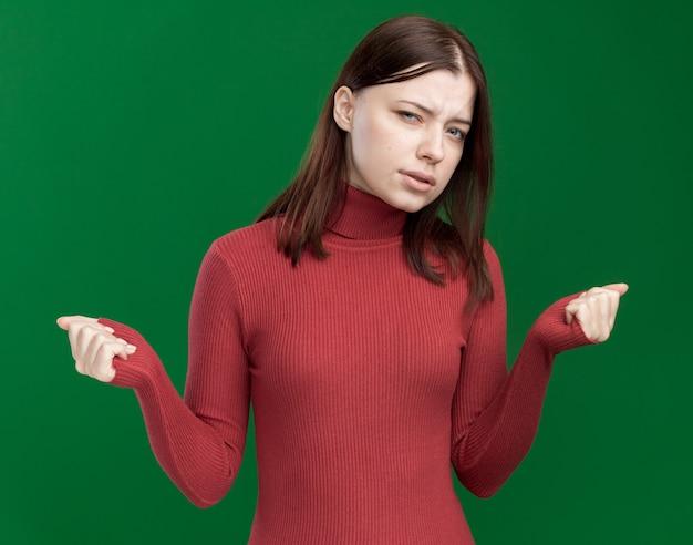 Wątpliwa młoda ładna dziewczyna z zaciśniętymi pięściami odizolowana na zielonej ścianie