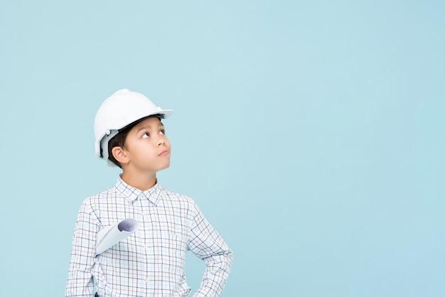 Wątpliwości inżynier chłopiec w biały kask patrząc w górę