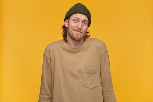 Wątpliwy mężczyzna, niepewny facet o blond włosach, brodzie i wąsach. ubrana w zieloną czapkę i beżowy sweter. wzrusza ramionami. nic nie wiem. pojedynczo na żółtej ścianie