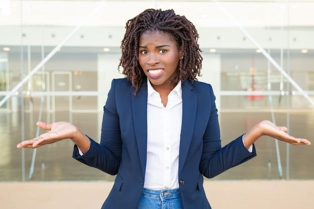Wątpliwy młody bizneswoman patrzeje kamerę