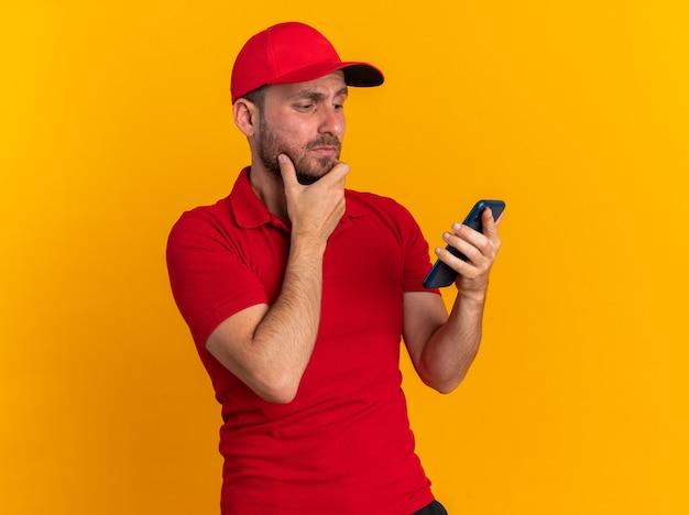 Wątpliwy młody kaukaski mężczyzna dostawy w czerwonym mundurze i czapce, trzymając rękę na brodzie, trzymając i patrząc na telefon komórkowy odizolowany na pomarańczowej ścianie