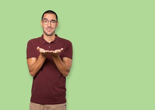 Wątpliwy młody mężczyzna trzyma coś za rękę