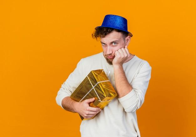Wątpliwy młody przystojny facet słowiańskich imprezowiczów w kapeluszu imprezowym, trzymając pudełko, kładąc dłoń na twarzy patrząc na kamery na białym tle na pomarańczowym tle z miejsca na kopię