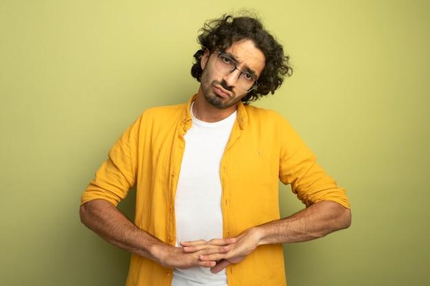Wątpliwy młody przystojny kaukaski mężczyzna w okularach, trzymając ręce razem na białym tle na oliwkowej ścianie