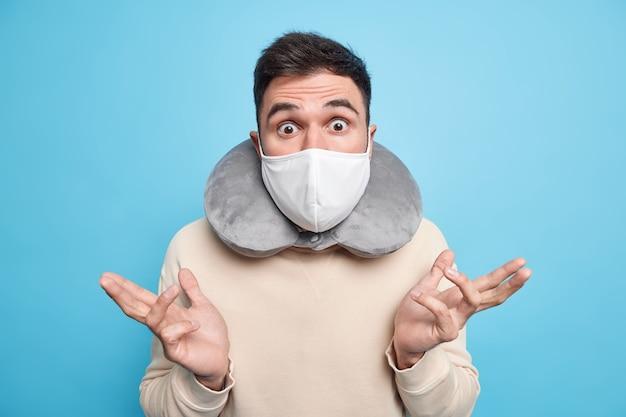 Wątpliwy niezdecydowany mężczyzna rozkłada dłonie na boki z niezrozumiałym wyrazem twarzy, wpatruje się w szok, nosi maskę ochronną podczas podróży podczas pandemii koronawirusa, do spania używa poduszki podróżnej