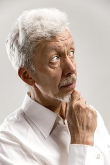 Wątpliwy, zamyślony mężczyzna coś sobie przypomina. starszy mężczyzna emocjonalny. ludzkie emocje, koncepcja wyrazu twarzy. pojedynczo na szaro