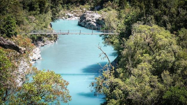 Wąwóz rzeczny z turkusowymi wodami i mostem obrotowym prowadzącym nad nim wąwóz hokitika nowa zelandia