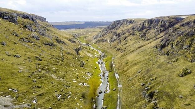 Wąwóz w górach mołdawii z pływającą rzeką, pochmurne niebo, pola w tle