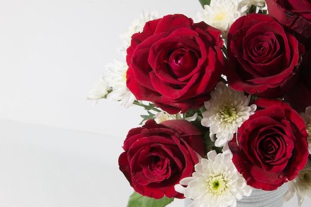 Waza bukieta czerwone róże w aluminiowym wiadrze na białym tle.