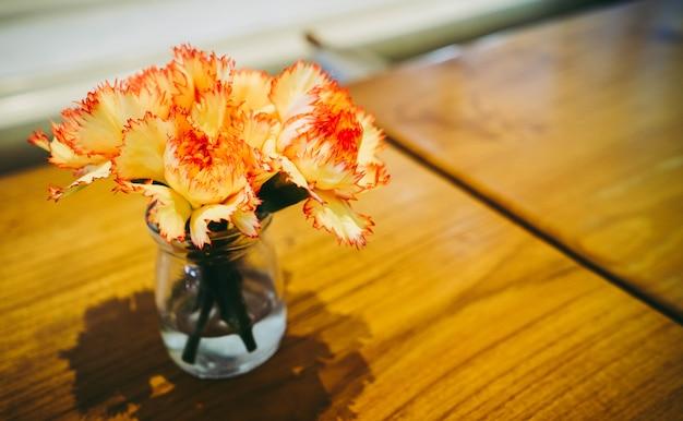 Waza, szkło piękny kwiat na drewnianym stole w kawiarni.