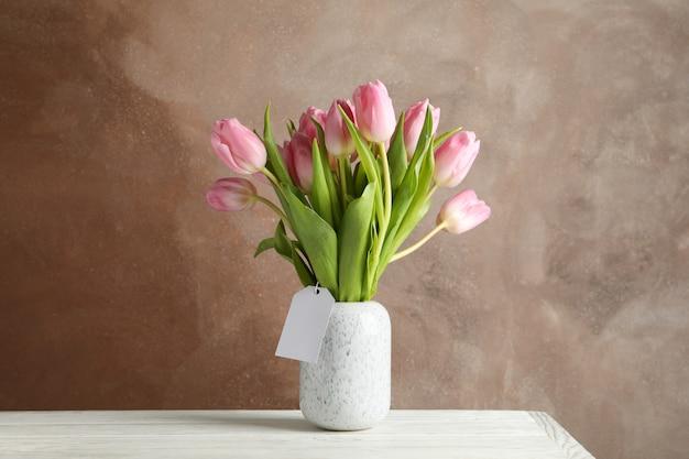 Waza z tulipanami na drewnianym stole, przestrzeń dla teksta