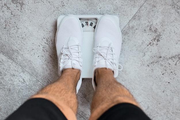 Ważenie męskie stopy stojące na wadze.
