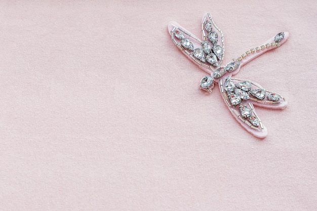 Ważka broszka z dżetów i koralików na różowym tle tkaniny