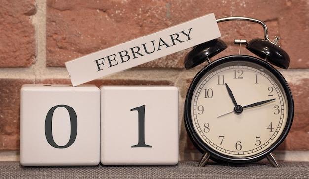 Ważna data, 1 lutego, sezon zimowy. kalendarz wykonany z drewna na tle ściany z cegły. retro budzik jako koncepcja zarządzania czasem.