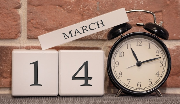 Ważna data 14 marca, sezon wiosenny. kalendarz wykonany z drewna na tle ściany z cegły. retro budzik jako koncepcja zarządzania czasem.