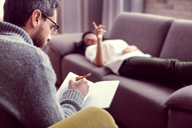 Ważna informacja. poważny, skupiony mężczyzna słucha swojego pacjenta podczas zapisywania informacji