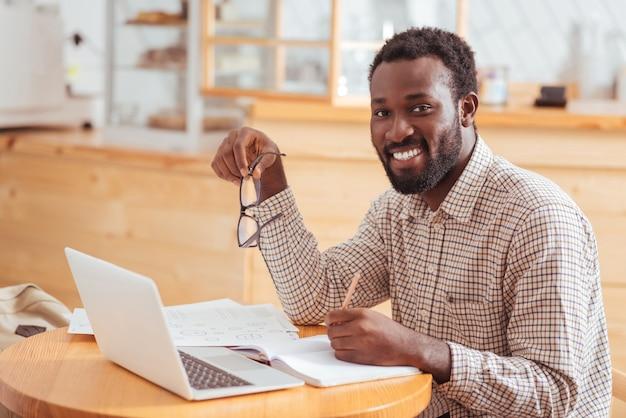 Ważna informacja. przystojny, wesoły mężczyzna siedzi przy stoliku w kawiarni i uśmiecha się do kamery, zapisując w notesie kluczowe informacje