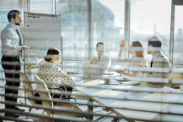 Ważna opinia. grupa sympatycznych młodych kolegów siedzących przy stole i słuchających wypowiadającej się uroczej kobiety
