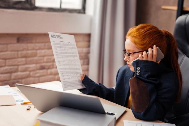 Ważna praca. ładna, poważna dziewczyna patrząca na dokument podczas rozmowy telefonicznej