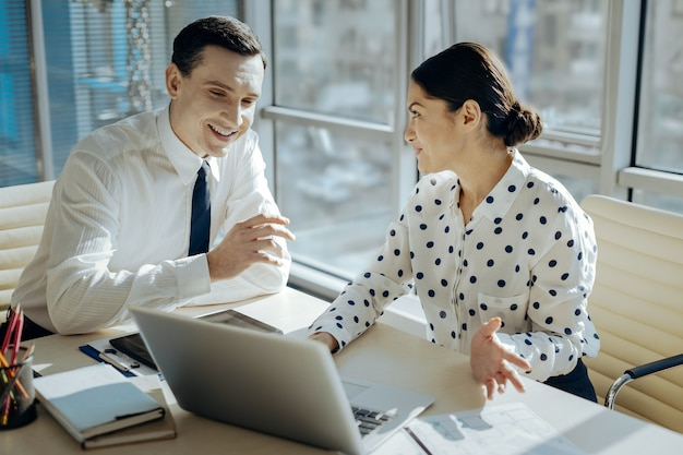 Ważna rada. ładna szefowa siedzi przy stole obok swojego kolegi i komentuje raport swoich pracowników, udzielając kilku rad