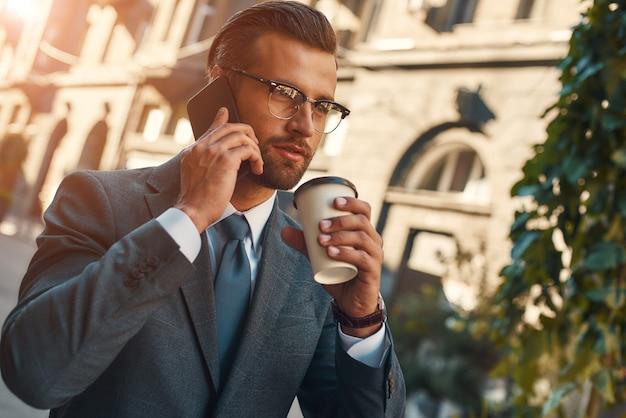 Ważna rozmowa młody i przystojny brodaty biznesmen w stroju wizytowym rozmawia przez telefon z klientem