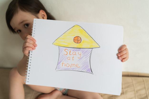 Ważne jest, aby pozostać w domu podczas pandemii. światowa kwarantanna koronawirusów. mała dziewczynka trzyma rysunek w ona ręki