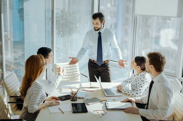 Ważne sprawy. przystojny młody szef stojący u szczytu stołu i rozmawiający z kolegami, prowadzący z nimi spotkanie biznesowe i omawiający istotne kwestie