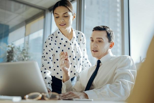 Ważne wskazówki. przyjemna młoda kobieta przeglądająca na laptopie prezentację kolegów i podsuwa mu kilka pomysłów na poprawę, podczas gdy mężczyzna jej słucha