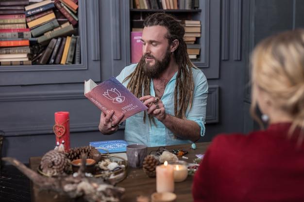 Ważny cytat. miły poważny człowiek otwierający stronę w książce podczas czytania ważnego cytatu