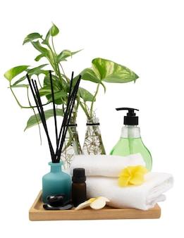 Wazon botaniczny zielony plamisty betel, kadzidełka, kwiat plumaria, białe ręczniki, świeca i olejek aromatyczny w spa lub łaźni na białym tle, aromaterapia spa wellness