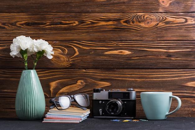 Wazon; książki; okulary; spinacz; filiżanka i retro kamera na czarnym biurku przeciw drewnianemu tłu