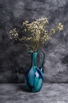 Wazon niebieski dzbanek z suszonymi białymi kwiatami łyszczec na ciemnym tle z teksturą, kąt widzenia