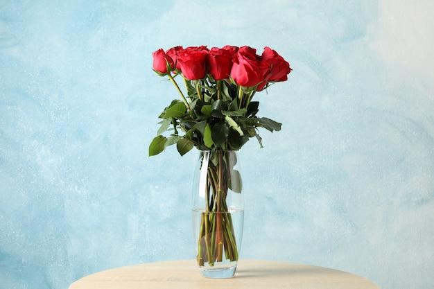 Wazon z bukietem czerwonych róż na drewnianym stole, miejsca na tekst