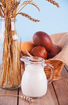 Wazon z bukietem łodyg pszenicy, słoik mleka i kosz z chlebem