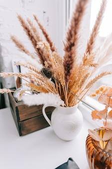 Wazon z bukietem suszonych kłosków i roślinnymi dekoracjami do domu na parapecie