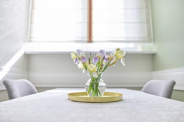 Wazon z bukietem żółtych i fioletowych irysów na stole przy oknie