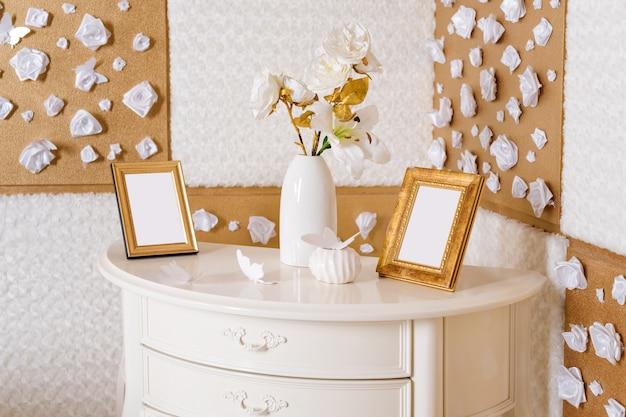 Wazon z kwiatami i ramkami do zdjęć na stole w białej i złotej sypialni. martwa natura, szczegóły dekoracji pokoju.