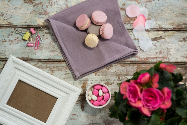 Wazon z kwiatami, makaroniki, cukierki i ramka na zdjęcia