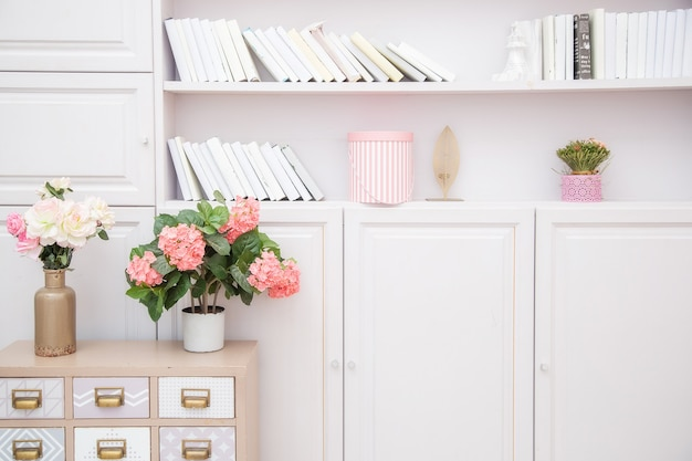 Wazon z kwiatami na komodzie obok regału w jasnoróżowym salonie w stylu skandynawskim.